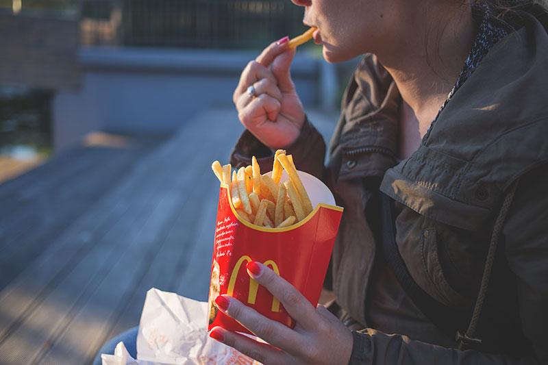 девушка ест картофель-фри